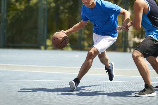 young asian adults playing basketball