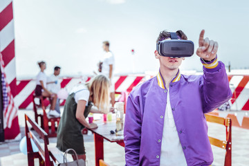 Virtual reality. Young man wearing electronic mask while pointing at something strange