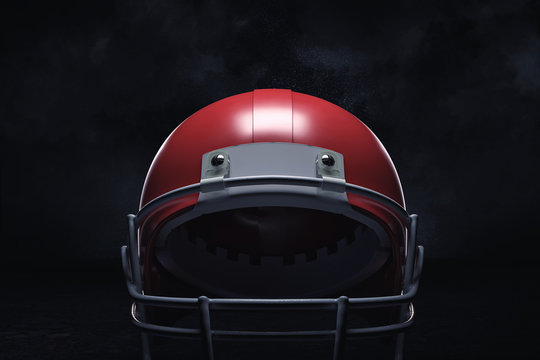 3d rendering of a red American football helmet with its front guard on a dark background.