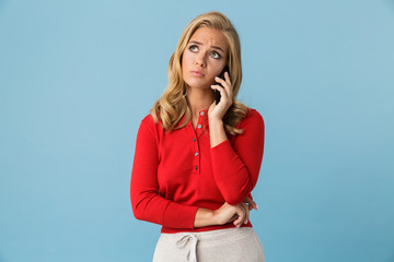 Portrait of disappointed blond woman 20s wearing red shirt talking on smartphone, isolated over blue background in studio