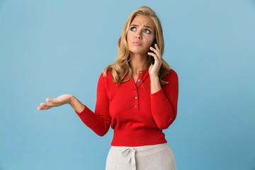 Portrait of upset blond woman 20s wearing red shirt talking on smartphone, isolated over blue background in studio
