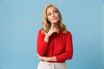 Portrait of affable blond woman 20s wearing red shirt looking aside at copyspace, isolated over blue background in studio