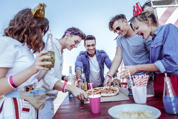 Fast food. Positive delighted students standing around table while having lunch on rooftop