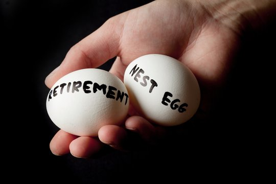 Hand Holding Two Eggs Marked Retirement And Nest Egg