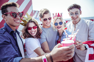 Colorful accessories. Handsome male person embracing his girlfriend while touching paper glasses with friends