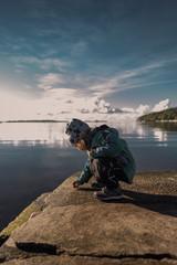 Paisaje otoñal con niña al lado del mar
