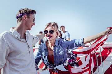 Red lipstick. Pleased girl keeping smile on her face while holding American flag