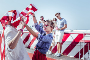 Lets dance. Charming female standing in semi position while holding American flag
