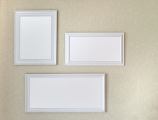 Three white wooden frames hanging on soft yellow wall mock up template