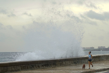 A woman jogs with a dog as waves splash at the seafront in Havana, after Hurricane Michael passed in western Cuba