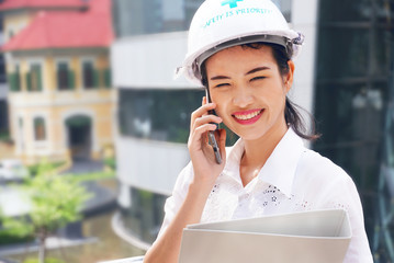 Engineer woman wear helmet safty and hold plan design stand at construction site working is talking on smartphone