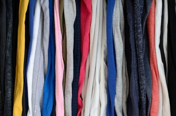 The colorful photo of messy clothes hanging in wardrobe that taking as background.