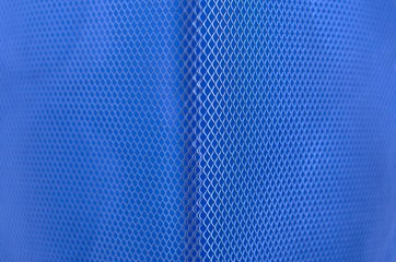 Blue color paper with partial focus of the grid pattern of paper bin that design as modern background and wallpaper.