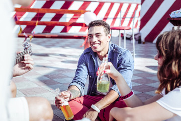 Sincere emotions. Happy dark-skinned man sitting near his friends and drinking beer