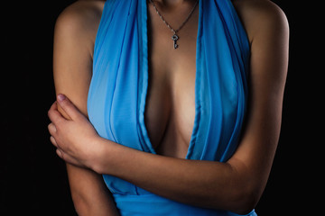 perfect sexy woman's body close up in a blue chiffon evening cocktail dress with big breasts with a silver pendant key around the neck. model silicone tits boobs on black background in studio shot