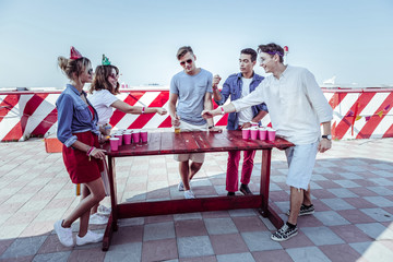 Group game. Handsome boy standing in semi position while talking to his partners