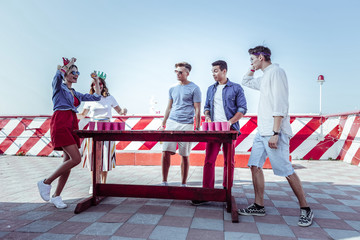 Express emotions. Attentive males looking at their friends while standing together near table