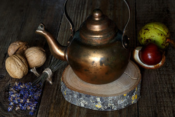 Copper kettle on wooden background
