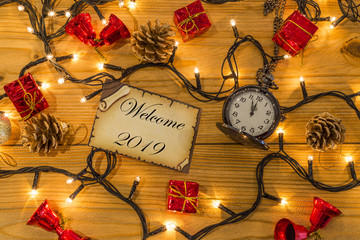 Greeting card for new year or christmas with pocket watch and christmas decors, lights top view