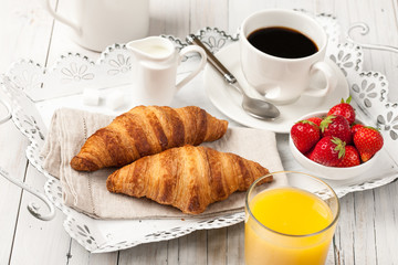 Breakfast with croissants, black coffee, orange juice and strawberries