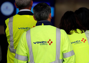 """The Vinci logo is seen on jackets during a visit a a mobile factory installed to produce tons of recycled asphalt near the A10 motorway in Gironde for a test for the first """"100% recycled"""" road by Eurovia"""
