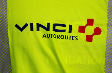 """The Vinci logo is seen on a jacket during a visit at a mobile factory installed to produce tons of recycled asphalt near the A10 motorway in Gironde for a test for the first """"100% recycled"""" road by Eurovia"""