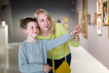 Smiling mom and son exploring paintings