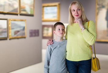 Cheerful mom and son exploring paintings