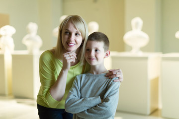 mother and son exploring old statues in museum