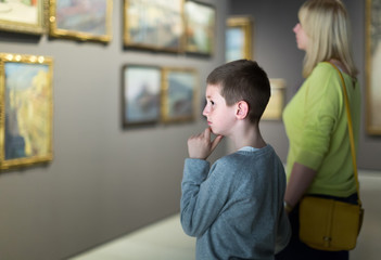 Mother and son looking at paintings in halls of museum