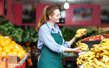 Seller woman is holding yellow bananas on her workplace in the market.