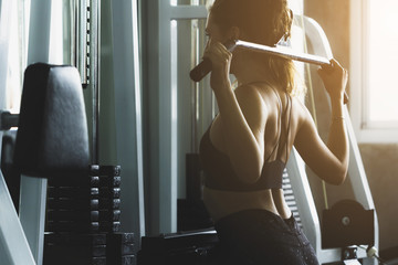 Closed up young woman working out in modern gym, with sun flare effect reflects on equipment.
