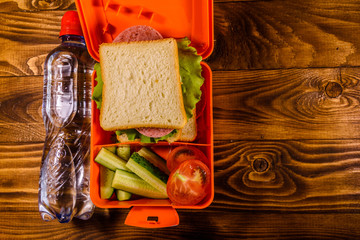 Bottle of water and lunch box with sandwich, cucumbers and tomatoes on wooden table. Top view