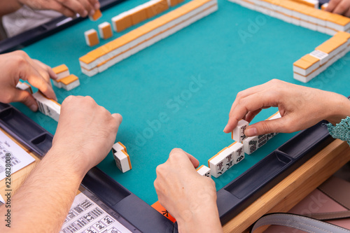 Company Of People Playing Mahjong On Green Table  Hands With