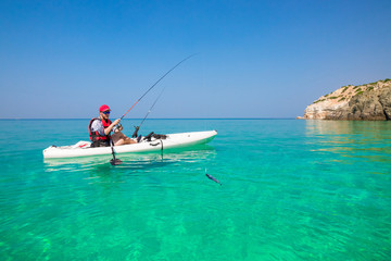 Fishing kayak in the sea on the islands. Man fisherman catch a fish with rod in the boat. Leisure activities on the water.