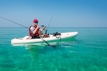 Man on a fishing kayak shows catch fish. Leisure activities on the sea. Fisherman on the islands.