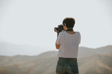 Woman in t-shirt taking a photo with a dslr camera in nature with daylight.