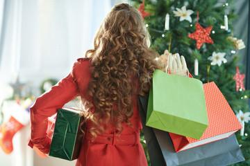 woman with shopping bags and Christmas gift near Christmas tree