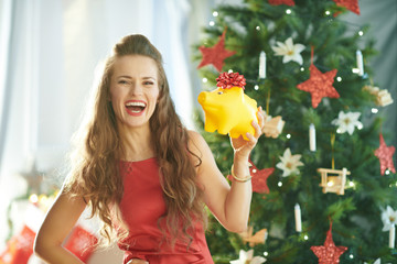 smiling young woman with yellow piggy bank near Christmas tree