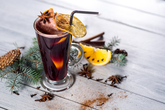A mulled wine in glass on the white wooden background