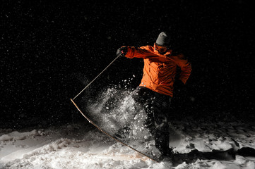 Snowboarder in orange sportswear and mask jumping on a snowy hill at night
