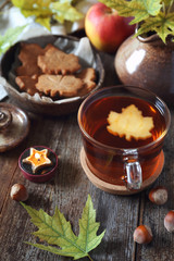 Autumn mood: cinnamon cookies in form of maple leaves, tea, red apple and yellow leaves