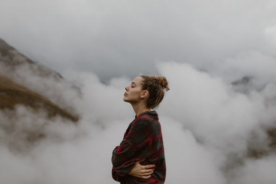 Woman above the clouds in the mountains