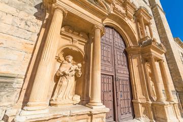 monk with child in arms statue in baroque exterior door of Parish of Santa Ana, landmark and monument in Penaranda de Duero, Burgos, Castile and Leon, Spain, Europe