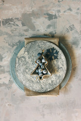 Christmas table set, plates decorated with bowl and jinglebells, on light blue rustic background.