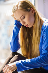 Sad depressed teen girl sitting on window sill