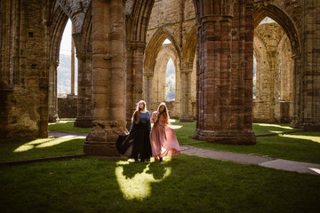 tow women in long dresses in an old abandoned welsh trintern celtic abby