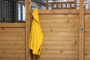 Yellow raincoat hanging in stable entrance