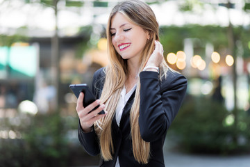 Young businesswoman using her smartphone to browse web content and sending messages outdoor
