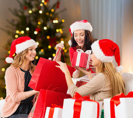 holidays and people concept - women in santa hats with gifts and shopping bags over christmas tree lights background